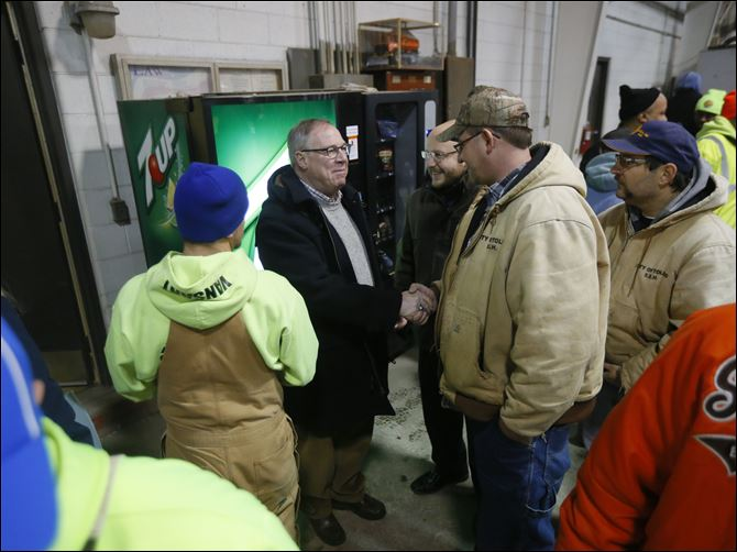 CTY collins7p streets workers Toledo Mayor D. Michael Collins, left, shakes hands with Bob Sadowski, right, as other employees of  The Division of Streets, Bridges & Harbor surround him at the headquarters on West Central Avenue today.