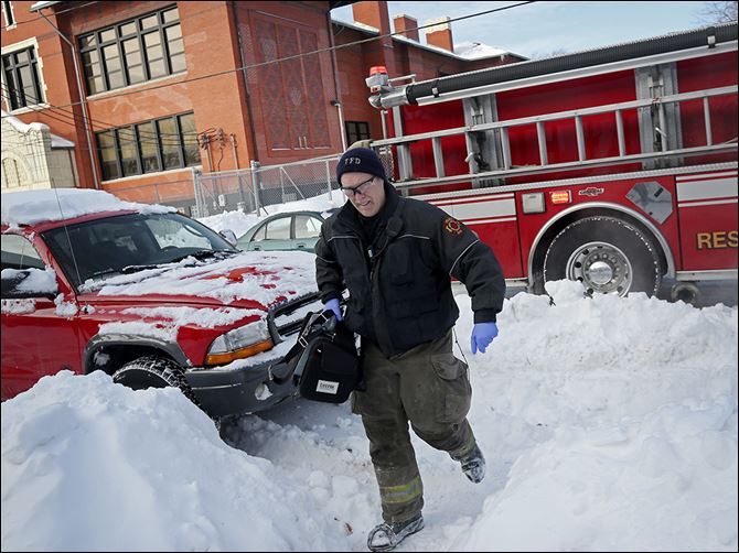 n4safety-3 Toledo firefighter Bill Bruss wades through the snow to carry a medical pack into a home for an ill person Tuesday in South Toledo. The unusually cold weather and snow has forced firefighters to contend with more calls from people unable to reach hospitals and made their routes harder.