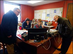 Toledo Mayor D. Michael Collins, left, and Joel Mazur, right, assistant chief of staff, listen as  Claudia Mitchell,  center left, and Shonna Doran, center right, dispatchers with The Division of Streets, Bridges & Harbor, explain how the GPS system works.