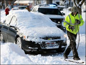 Jim Piasecki of Piasecki Service, Inc. prepares to tow a car off Olson Street into the owner's drive way so city crews can plow the street Tuesday.
