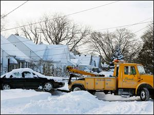 A Piasecki Service, Inc. tow truck moves a car off Olson Street into the owner's drive way so city crews can plow the street.