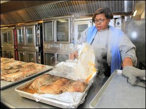 Mary Bourn of Toledo cooks pork roasts for meals Tuesday at the Margaret Hunt Senior Center,  the site of meal preparation and distribution for area residents in Toledo.