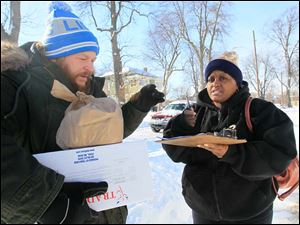 Grace Smith of Toledo, right, signs for a delivery of frozen meals and a small bag of