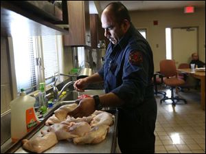 Toledo firefighter Alan Campos washes chicken as he prepares to make dinner at the Station 9 on Tuesday.