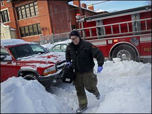 Toledo firefighter Bill Bruss wades through the snow to carry a medical pack into a home.