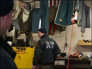 Toledo firefighter Bill Bruss passes by drying firefighting clothing hung inside the truck bay Tuesday at the Station 9 firehouse in South Toledo.