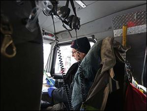Toledo Fire Department Capt. Tom Phillips fills out paperwork in the truck after responding to a call from an ill person.