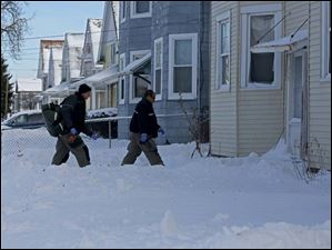 Toledo firefighters Graham Johnson, left, and Alan Campos, right, head into a home to respond to a medical call.