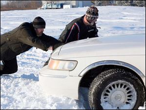 Mike Butzin, left, and Mark Oden, right, from Point Place, push Marie Hayter's vehicle out of a snowbank where she was stuck on Suder Avenue in Erie, Mich. Tuesday.