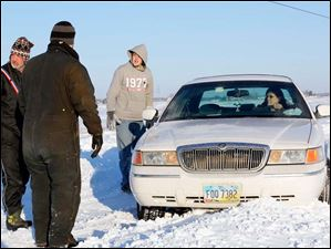 Mark Oden, left, and Mike Butzin, center left, in striped hat, from Point Place, stop to help Jacob Hayter, right center, and his mother Marie Hayter, right, of Temperance, Mich., get out of a snowbank where they were stuck on Suder Avenue in Erie, Mich. Tuesday.
