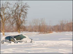 A snow-submerged car abandoned on Suder Avene near Lotus Drive in Erie, Mich., Tuesday.
