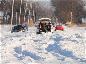 Three vehicles try to dig their way out of the snow on Suder Avenue near Lotus Drive in Erie, Mich., Tuesday.