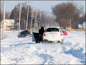 Three vehicles try to dig their way out of the snow on Suder Avenue in Erie, Mich.