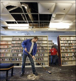Patrick Richardson of Polygon cleans up damage at the  Heather-downs branch of the Toledo-Lucas County Public Library. Water covered much of the floor after the cold caused a pipe to burst.