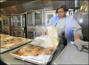 Mary Bourn of Toledo, cooks pork roasts for meals for Wednesday at The Margaret Hunt Senior Center, the site of meal preparation and distribution for area residents in Toledo.