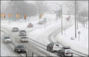 Traffic moves in cold and snowy conditions Tuesday along U.S. 31 near West Grand Traverse Bay in Traverse City, Mich.