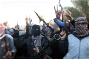 Gunmen gather in a street as they chant slogans against Iraq's Shiite-led government and demanding that the Iraqi army not try to enter the city in Fallujah, 40 miles (65 kilometers) west of Baghdad, Iraq, Tuesday, Jan. 7, 2014.