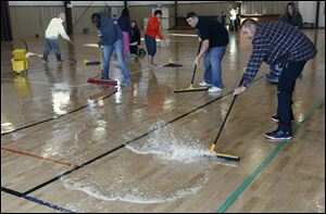Mario Rodriguez, right, is among about a dozen people who volunteered  to dry the gym floor  Wednesday at the Perrysburg Heights Community Center . The floor flooded during a frozen water pipe break.