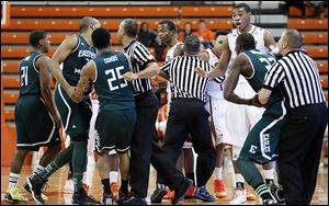 Officials break up a skirmish between Bowling Green and  Eastern Michigan players in Wednesday night's MAC opener.