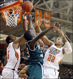 Bowling Green's Spencer Parker, left, and Richaun Holmes battle Eastern Michigan's Glenn Bryant for the ball in Wednesday night's game at the Stroh Center. The Falcons fell to 6-8.