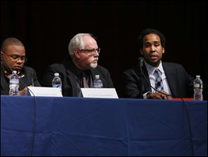 David Johns, right, speaks as University of Toledo student Christopher Scott, left, and Dale Snauwaert, University of Toledo, listen, during the Toledo Community Coalition's public forum on combating racism at t
