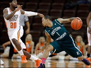 BGSU's Jehvon Clarke (20) defends against  Eastern Michigan University guard Mike Talley (1).