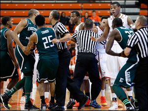 Officials break up a skirmish between Bowling Green State University and  Eastern Michigan University players at the Stroh Center.