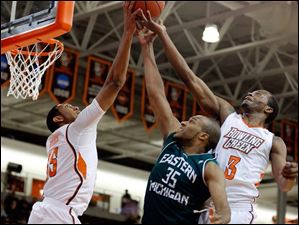BGSU's Cameron Black (35) and forward Spencer Parker (3) battle Eastern Michigan University guard Daylen Harrison (35) for a rebound.