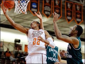 BGSU guard Richaun Holmes (22) goes to the basket against  Eastern Michigan University center Da'Shonte Riley (10).