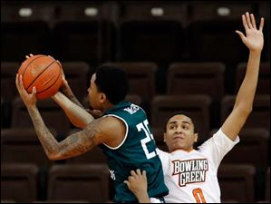 BGSU center Josh Gomez (0) and guard Anthony Henderson (2) defend against  EMU's guard Darell Combs (25).