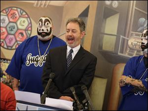 Insane Clown Posse members Joseph Bruce, back left, and Joseph Utsler, right, listen as Michael J. Steinberg, legal director for ACLU of Michigan, center, announces that the ACLU has filed a lawsuit against the U.S. Justice Department over a 2011 FBI report that describes the rap-metal duo's devoted fans, the Juggalos, as a dangerous gang.