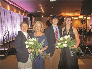 Joe DuPuis,left, and Noah Best, second from right, present flowers to their mothers Carol and Sara who served as volunteer chairpersons of the 2013 An Elegant Knight, a fund-raiser for St. Francis de Sales