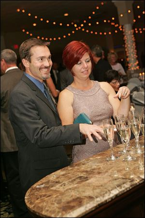 Andy and Michele Kress contemplate which glass to select. Guests at the Central Catholic High School fund-raiser could purchase a glass of champagne that contained a 1-carat cubic zirconia, but one held a 1-carat diamond.
