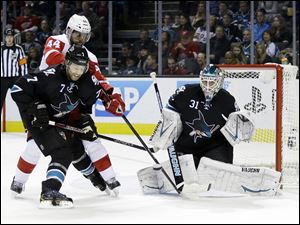 San Jose Sharks goalie Antti Niemi (31) stops a shot on goal next to teammate Brad Stuart (7) and Detroit Red Wings' Todd Bertuzzi (44) during the second period in San Jose.