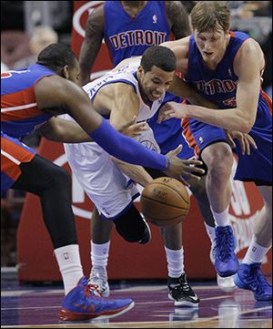 The Pistons' Greg Monroe, left, and Kyle Singler, right, scramble for a loose ball against the 76ers' Michael Carter Williams. Singler had 16 points and Monroe added 15.