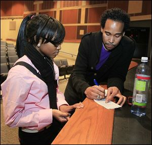 Woodward High junior Lyric Carter, left, speaks with David Johns after his talk at the school.