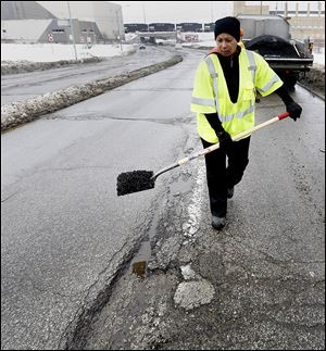 Toledo city worker Paula Williams patches potholes on Berdan Avenue near Detroit Avenue on the city's north side.