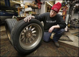 Par Roslin, co-owner of Majestic Automotive in Toledo, shows a 20-inch wheel that was damaged by a pothole. He said his shop has been busy with people who need tires worked on after hitting potholes.