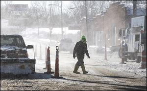 A city worker battles blowing snow in downtown Toledo. Monday's conditions were blamed on the polar vortex.