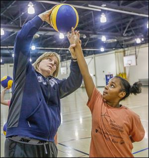 Rockets basketball head coach Tricia Cullop shows Janet Whitney proper shooting form during Girls Basketball Skills Camp. Ms. Cullop, who volunteered her time, says helping the community is a 'win-win.'