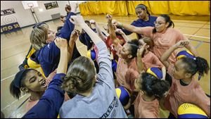 UT head coach Tricia Cullop shows the girls how to cheer in a huddle during Girls Basketball Skills Camp at the University of Toledo's Health Education Center.