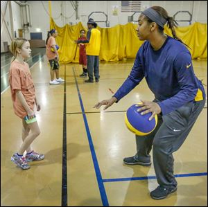 Emma Gall gets dribbling lessons from UT player Mariah Carson during Saturday's Basketball Skills Camp. The Saturday camp is sponsored by the Toledo Community Recreation Program.