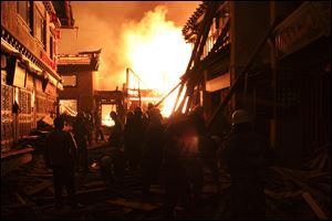 Firefighters fortify a wooden building Saturday while a fire ravages ancient Dukezong town in Shangri-la county, in southwestern China's Yunnan province.