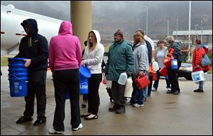 People wait in line for water from a 7,500-gallon tanker truck brought in from Washington, Pa.