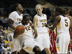 Toledo's Brianna Jones, left, picks up teammate Janice Monakana after Monakana was fouled as Olivia Braun and Janelle Reed-Lewis look on.