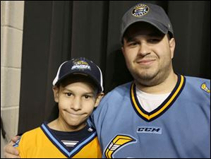 Anthony, 10, left, and his father Gary Stiff, of West Toledo attended the game. Gary Stiff was declared the team's millionth fan since the beginning of the 2009 season.