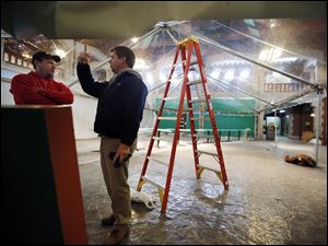 Mike Baumgartner of Toledo Tent, left, talks with Todd Cereghin, small projects manager at the Toledo Zoo, about a new butterfly exhibit.