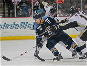 The Walleye's Alden Hirschfeld pushes through Wheeling's Nick D'Agostino, back, and Drew Schiestel.