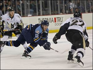 The Walleye's Travis Novak lunges as he sends the puck flying past Wheeling's Nick D'Agostino.