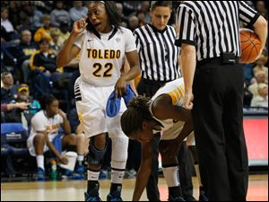 UT's Andola Dortch indicates to the fans that teammate Janelle Reed-Lewis had lost a contact, she had spotted it, and now Reed-Lewis is picking it up near two officials.